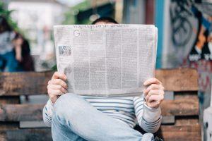 Mies lukemassa lehteä.